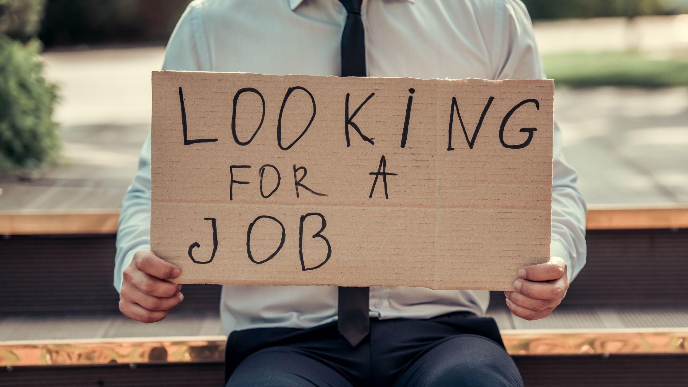 """Das Bild zeigt einen Mann, der einen Karton vor sich hält, auf dem steht: """"Looking for a job""""."""