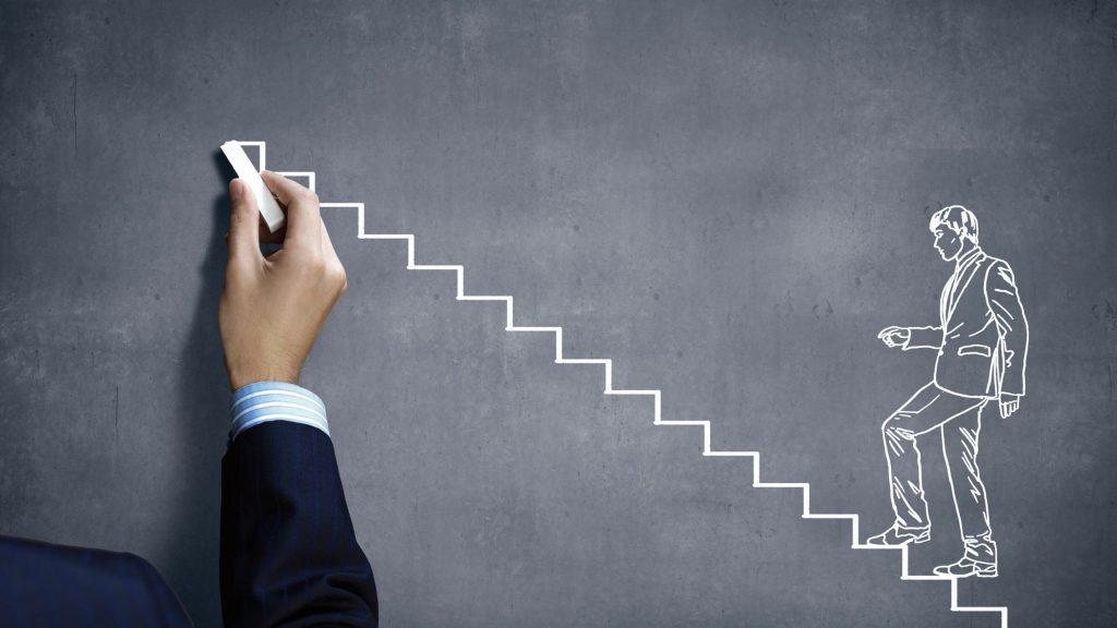 Illustration zeigt eine Tafel auf der ein mit Kreide gemalten Mann auf einer Treppe zu sehen ist..